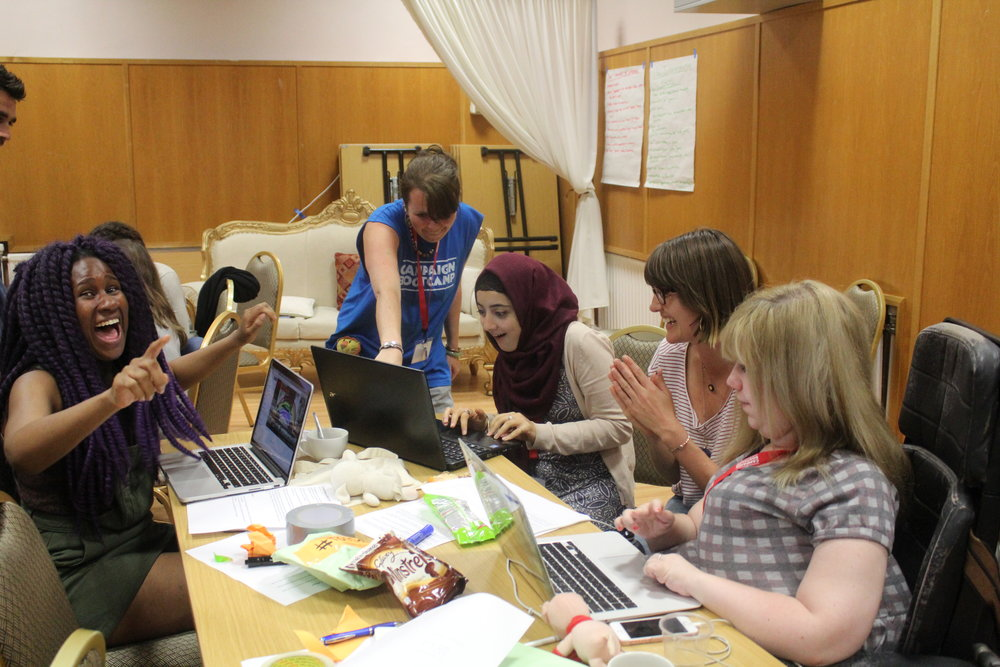Image Description: A group of Bootcampers sit round a table working on their laptops. Samia sits to the left of the picture looking excited.