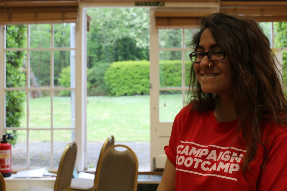 Image Description: Melissa grins while wearing a Campaign Bootcamp t-shirt. The garden is in the background.