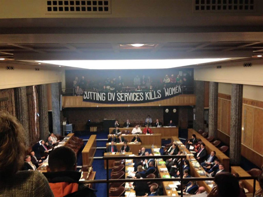 Sisters Uncut disrupt a councillors' meeting in Portsmouth to protest cuts to domestic violence services in 2016.