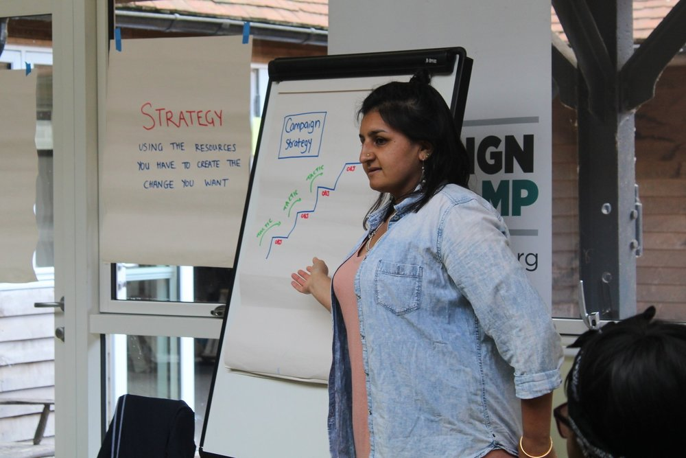 Image Description: Bootcamp trainer Guppi points to a flipchart pad with 'Campaign Stategy' written on it.