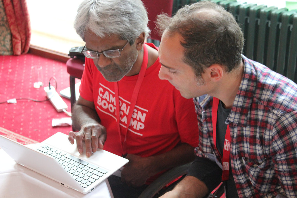 Image Description: Kumar and Alfonso work together on a laptop. Kumar is wearing a Campaign Bootcamp t-shirt.