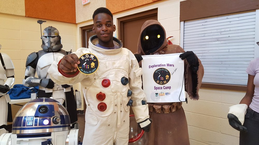 Kia's son, Elijah, wearing an Apollo mock-up suit at Kia's first space camp to promote the mission to Mars.