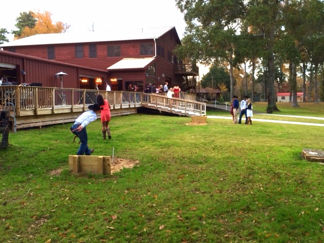 A group of guests relax and play a game of Horseshoes.