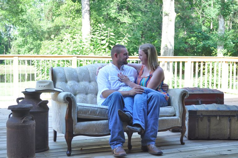 The beautiful couple poses on a rustic couch out on our deck.