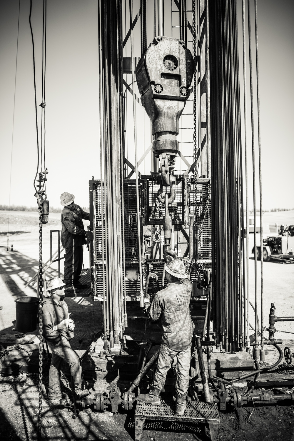 A workover crew removing four miles of pump rod to repair a well. The work is unending, incredibly physical and dangerous, as witnessed by the cast on the broken arm of the attending supervisor.