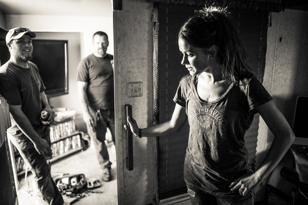 A woman, wife to an oil industry worker, stands in her travel trailer home while her husband and his friend talk and drink beer in the adjacent makeshift den.
