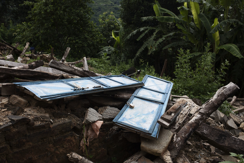Remains of a door sit atop of rubble. Outside of Duwachaur village, Sindupalchowk district, Nepal. July 27, 2015.