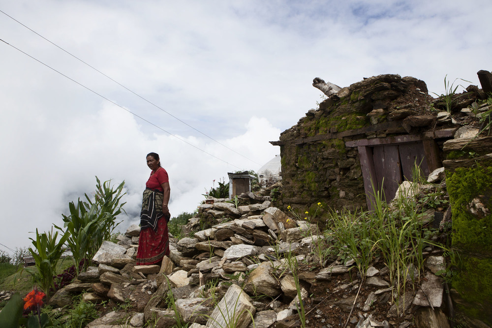 A Villager stands amongst rubble.  Tauthali Village, Sindupalchowk District, Nepal. August 5, 2015.
