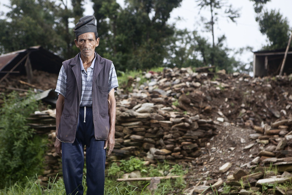 "Prembahadur Shrestha age 65 stands where his home once was. ""When I came here to see my home, I couldn't see, I just cried. Now I am not feeling so good just thinking how can I rebuild how to live again."" Tauthali Village, Sindupalchowk District, Nepal. August 5, 2015."