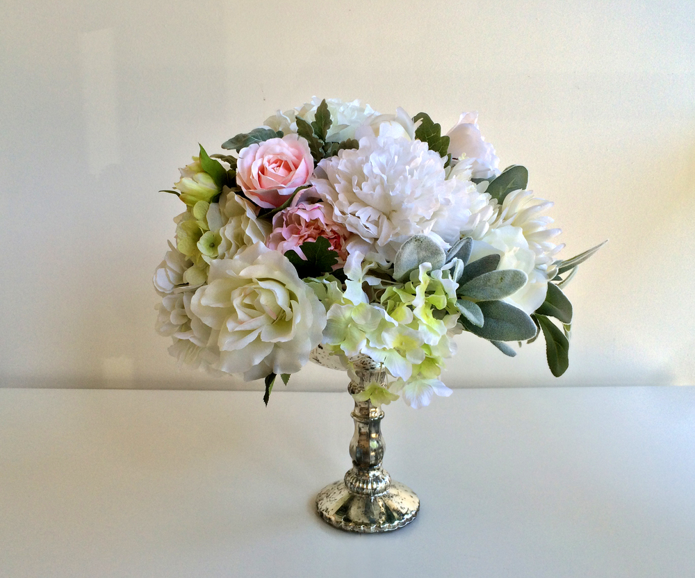 "Silk flower arrangement sits in an antique silver mercury glass footed bowl. Size: H16"", W10"".  From $245.00"