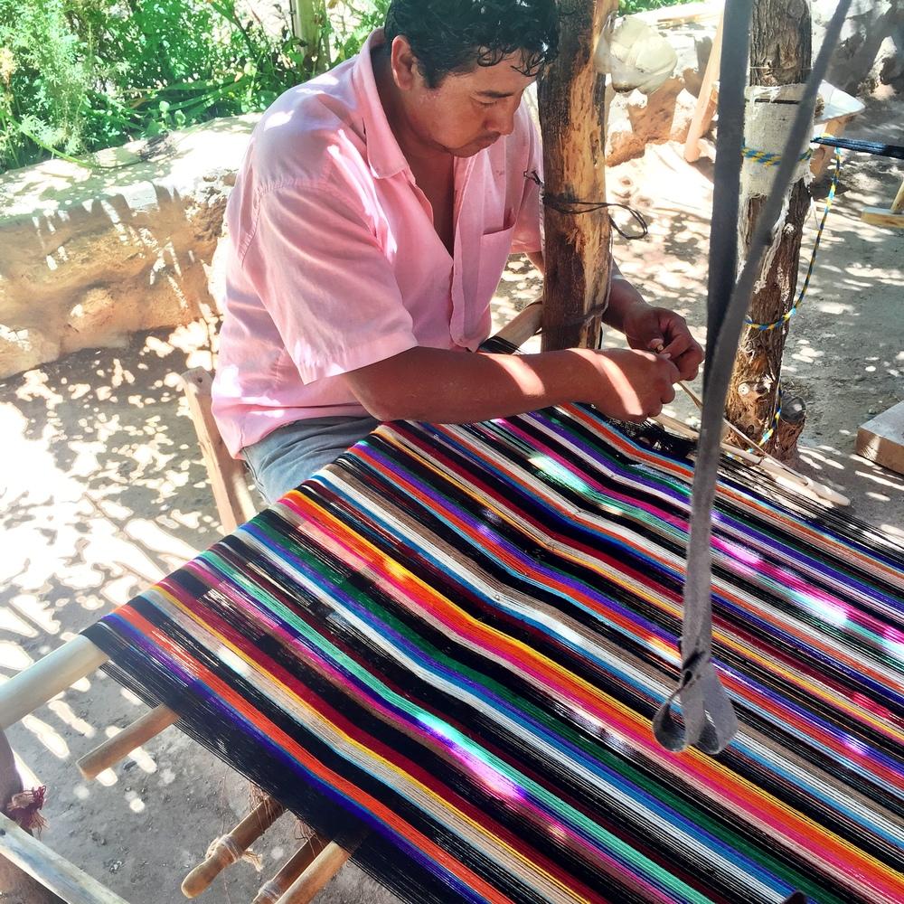 Un cousin d'Arnaldo ajustant ses fils sur son métier à tisser