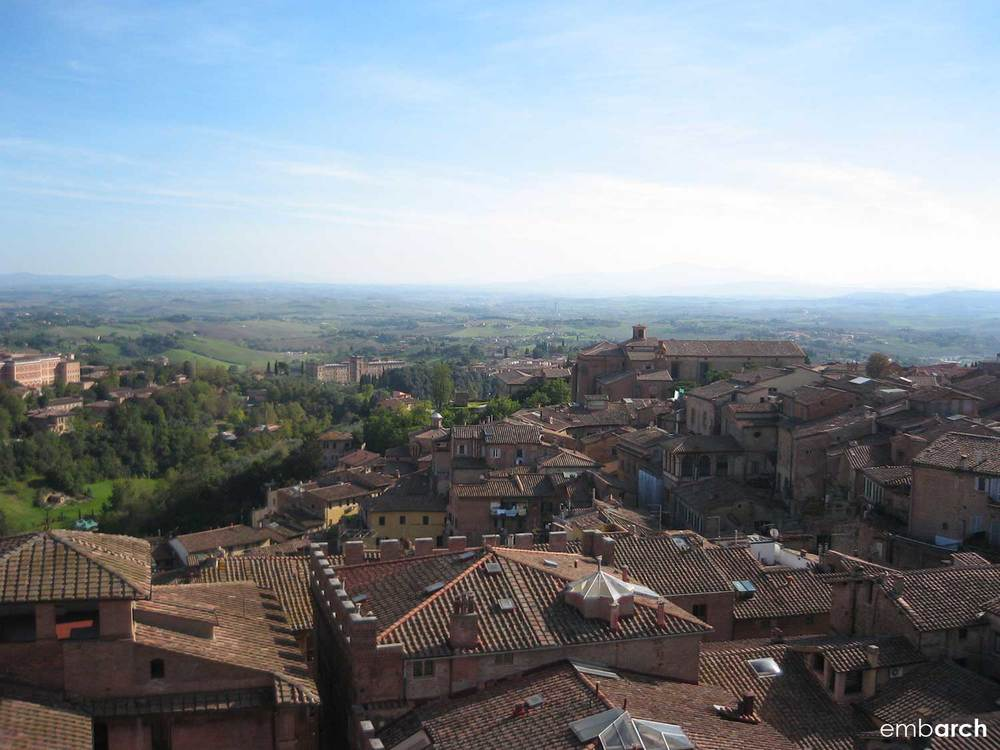 View of the Tuscany hills over the roof tops of Siena, Italy.