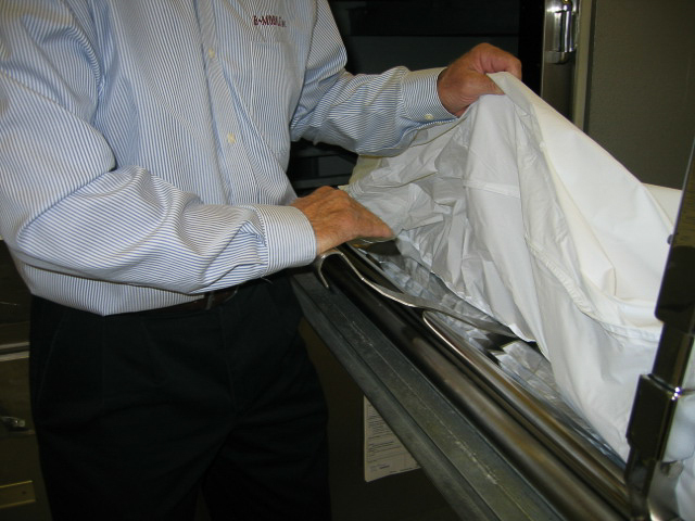 2. BodyScoop EXTENSION placement shown using heel of the hand to push extension in, under the sheet and over top of scoop.
