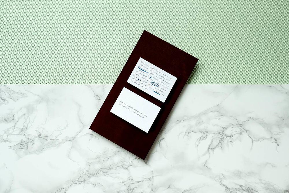 Visitenkarten auf schwarzem Umschlag auf hellgrünem Hintergrund.