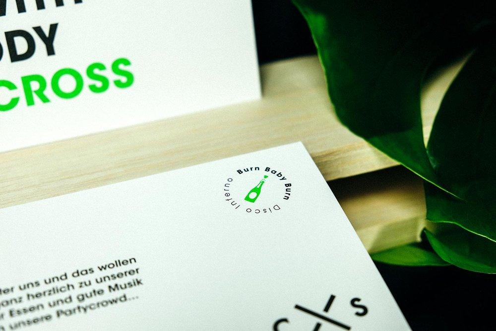 Nahaufnahme auf Holzstempel für stempelbares Logo auf weißer Grusskarte auf grüner Hintergrund.