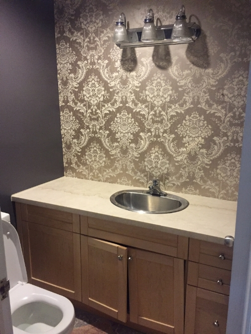BEFORE: The existing vanity was simply too large and the placement made for an awkward layout with limited storage. The wallpaper, lighting & flooring were dated and needed a modern refresh.