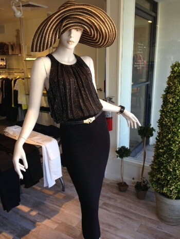 We love the lines of this long tapered back zipped pencil skirt topped with a beaded silk racer cut blouse tucked in loosely. The bronze draped rolled edge hat and slim stitched belt add a touch of whimsy to the look.