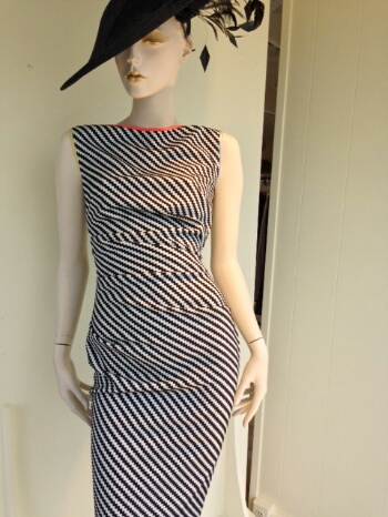 This black and white asymmetric stripe draped dress is piped at the neck and arms holes with fun pops of coral, yellow and ice blue. This black feathered fascinator is the perfect accessory to get you Derby Ready!