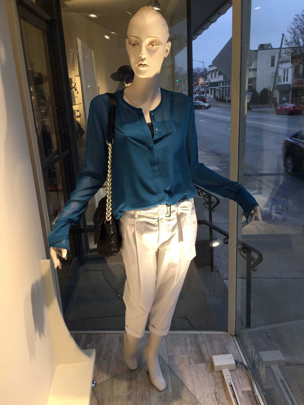 We always love a white cotton boyfriend trouser for summer, like this one from Strenesse, paired back to a teal silk sheer blouse from Schumacher over a black lace camisole.""