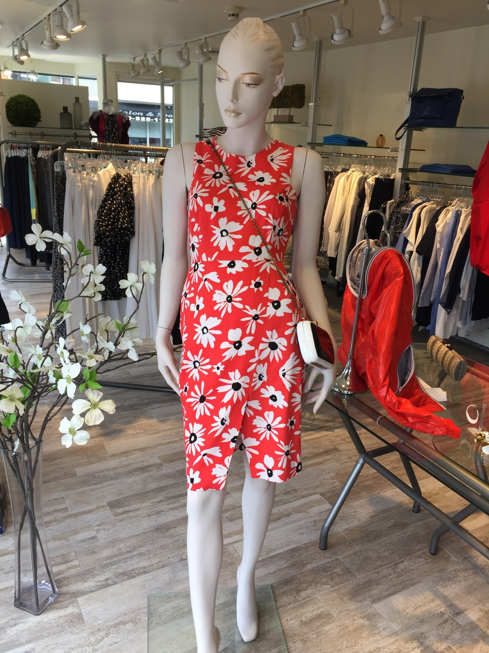 This daisy print dress from Whit has just the right pop of color for a spring or summer event.  We love all of the little details....the split pencil, the squared armhole and the open back.