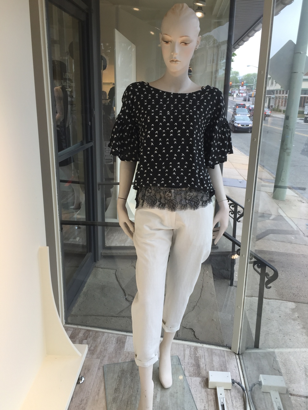 We love this little flutter sleeve top with the cross-stitched detail from up and coming designer, Litke. We layered it over a black lace cami to add a bit of length, and a linen ivory trouser from Crippen.