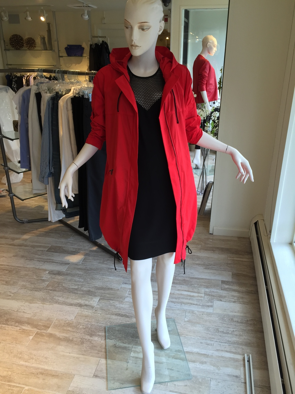 Stand out in the rain with a pop of color from Sarah Pacini. This coat can be rolled into a ball and packed for easy traveling. Here we have it over a mesh neck easy cotton dress from L'Agence.