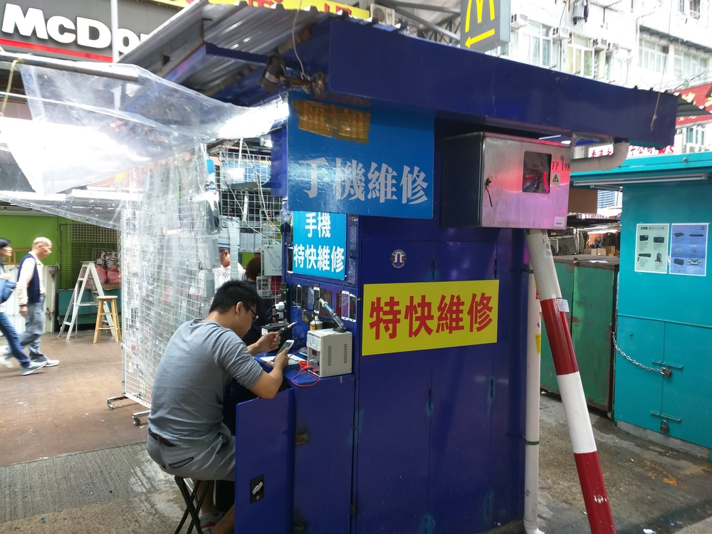 Above:  Roadside cell phone repair stand.  Apliu St, Shumshuipo, Hong Kong.  It is estimated that 1/5 of sub-Sahara African cell phones passes through Hong Kong