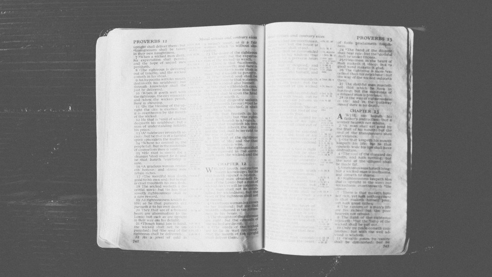 Black and white bible open on wood table.