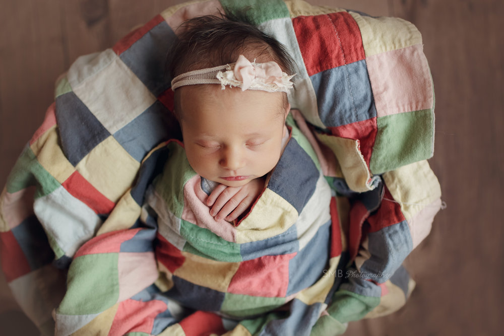 Newborn girl wrapped in colorful quilt in a bucket in Blanchard, Ok