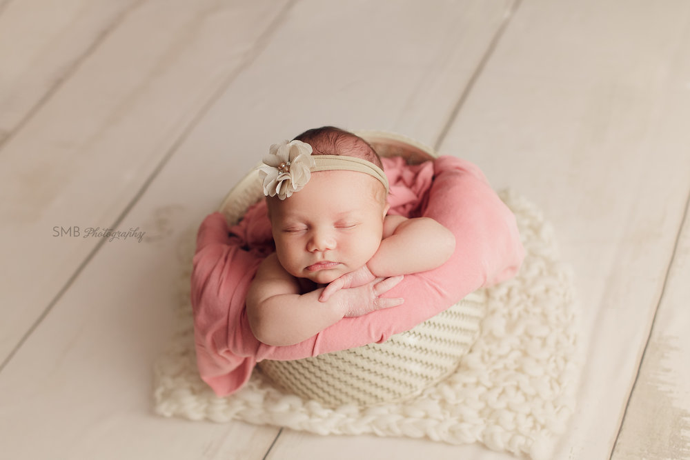 Baby girl facing camera in cream basket on cream floor in Edmond, Oklahoma