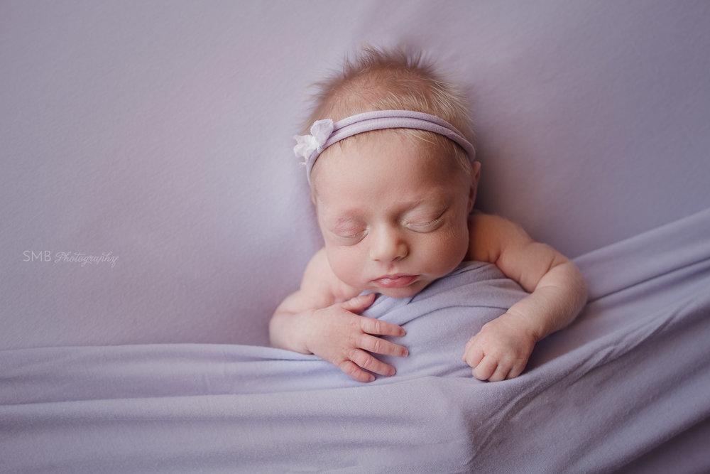 Newborn girl on purple blanket with purple headband