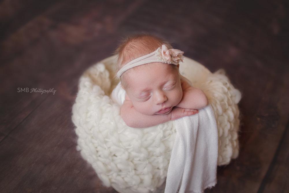 Newborn girl in bucket facing camera wearing pink bow headband in Okc