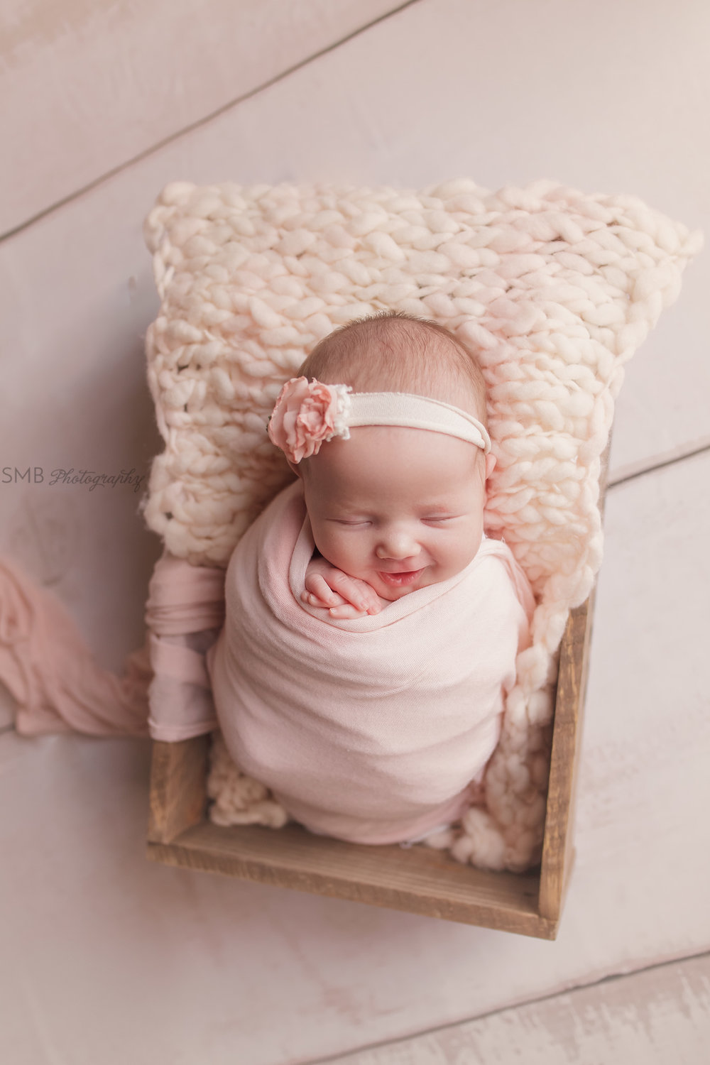 Newborn girl in wood box wearing pink