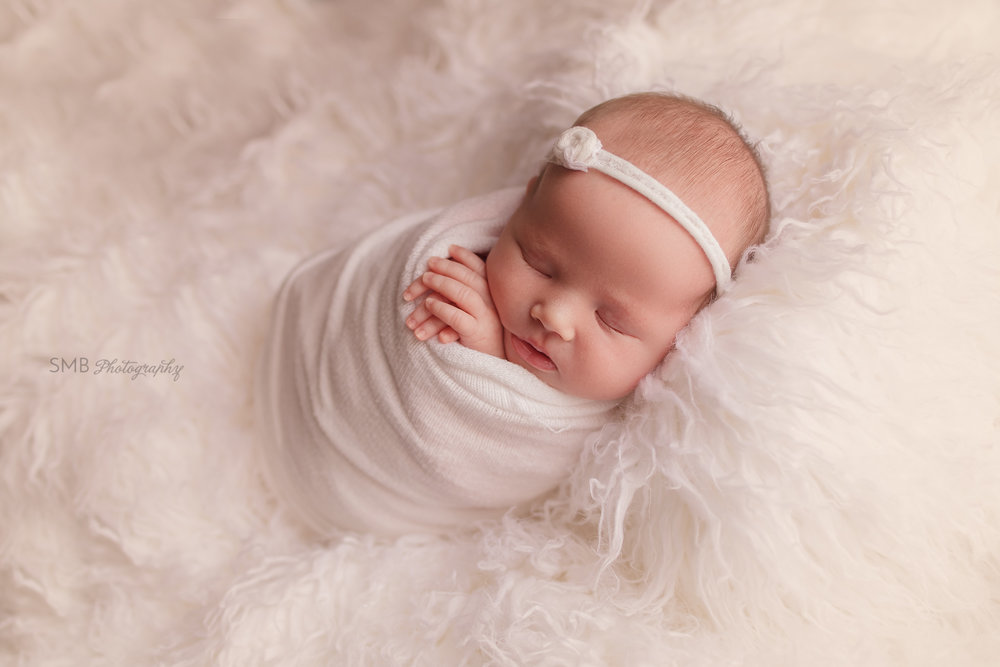 Newborn girl wearing white headband on white flokati