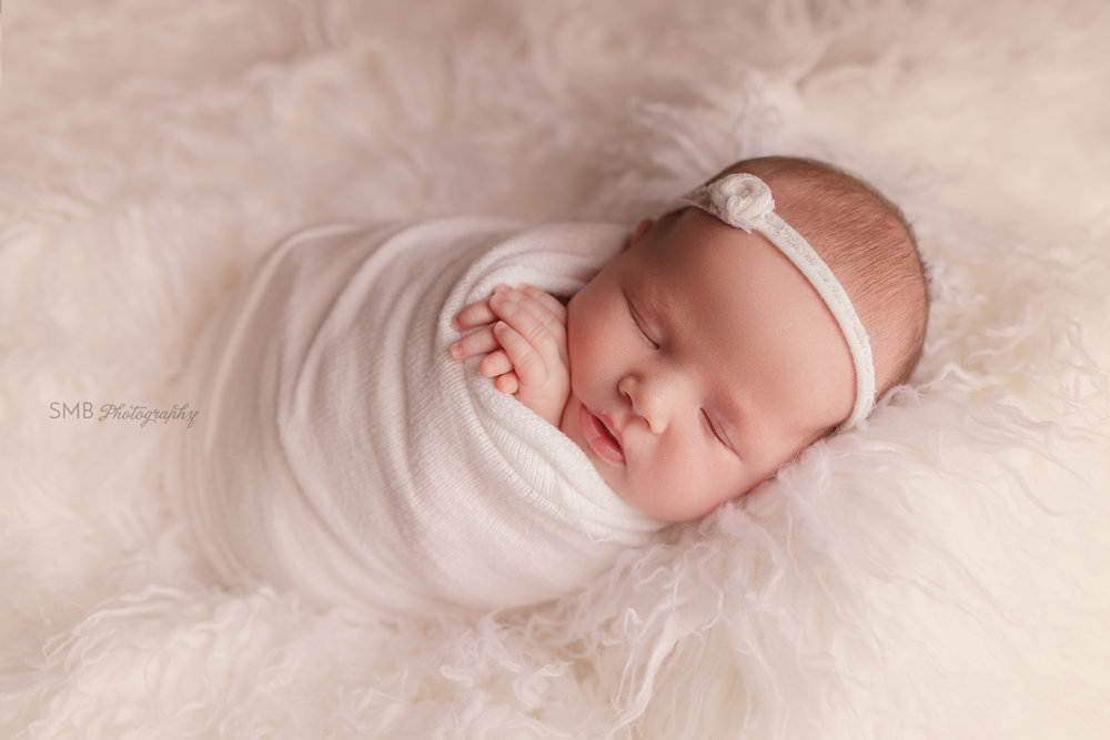 Newborn girl sleeping on white flokati