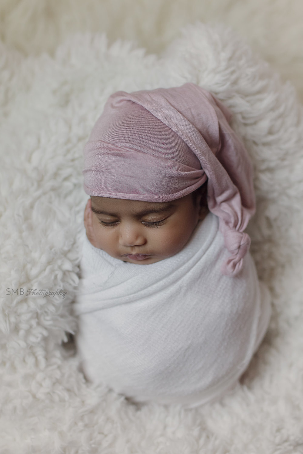 Newborn sleeping on fuzzy white blanket