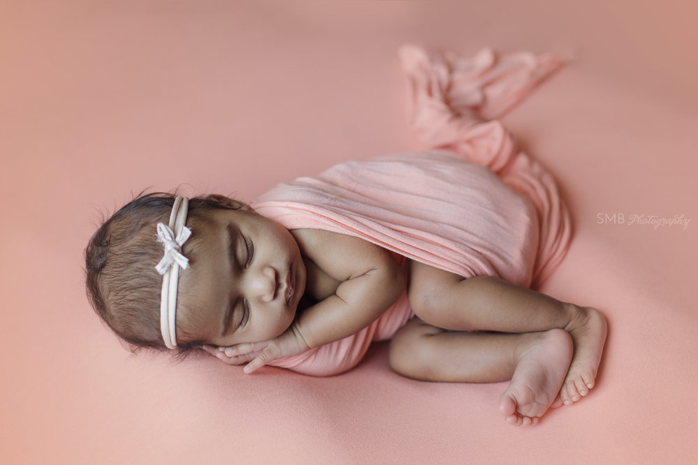 Newborn laying on side, wearing a little bow