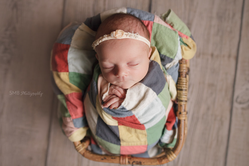 Newborn girl wrapped up in colorful quilt