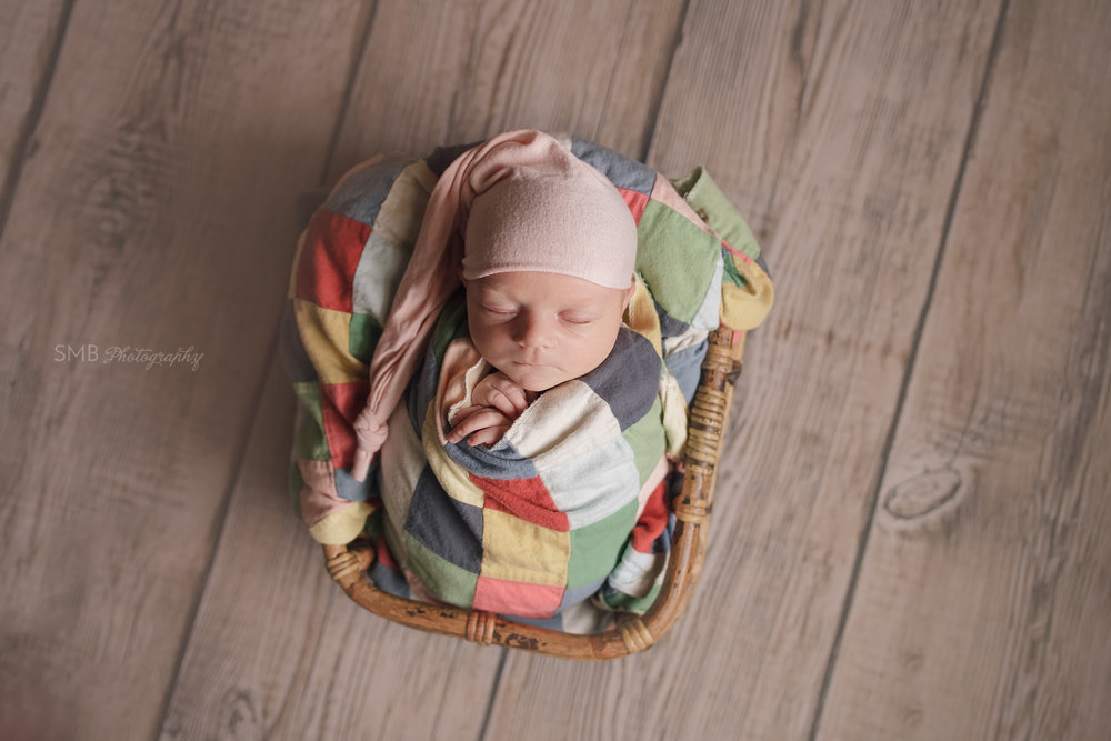 Newborn girl wearing pink sleep hat