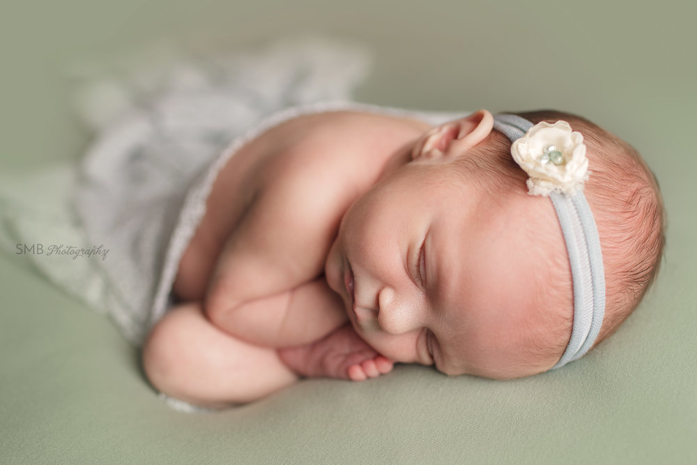 Newborn girl curled up on sage green blanket