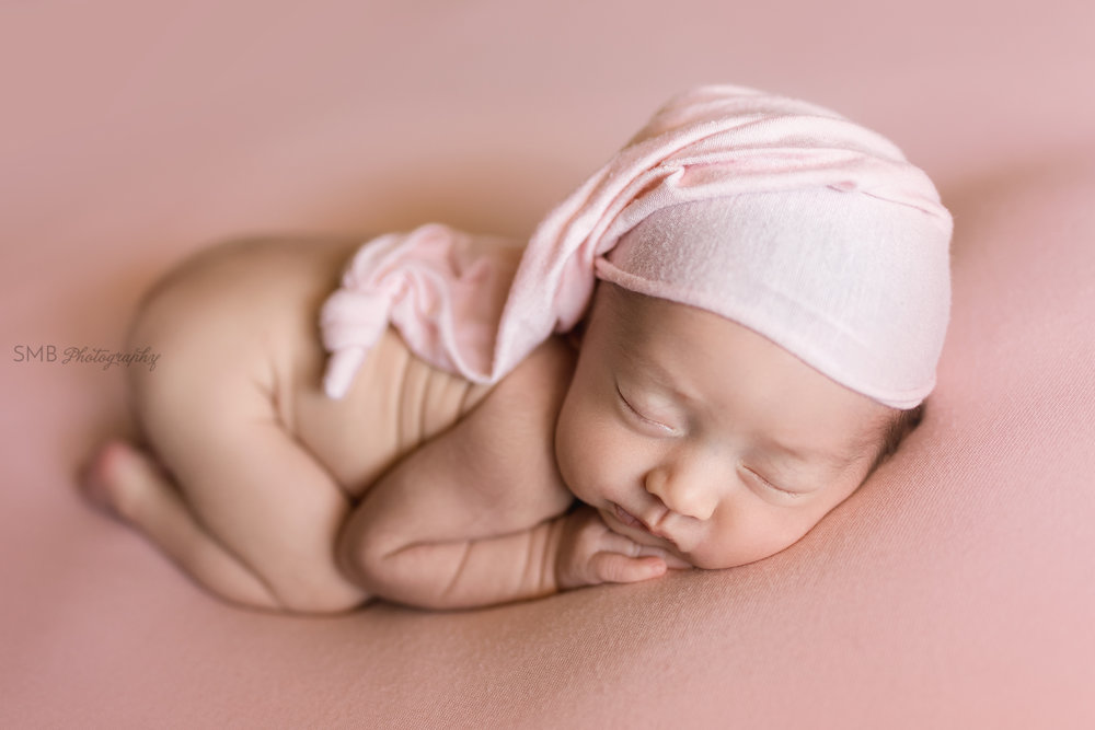 Newborn girl on pink blanket wearing sleepy cap