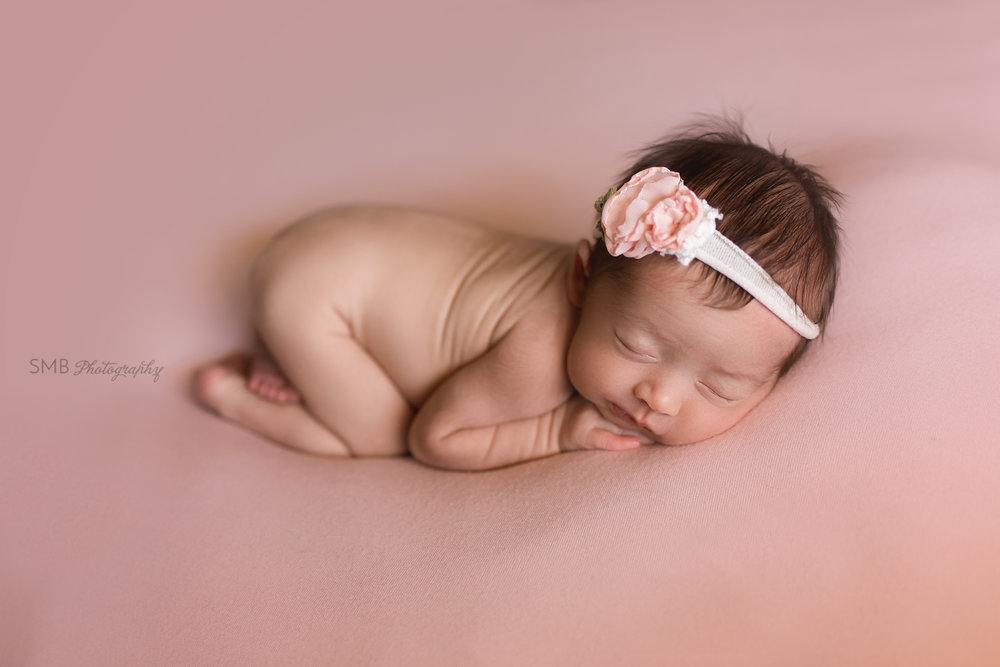 Newborn girl on pink blanket wearing flower headband
