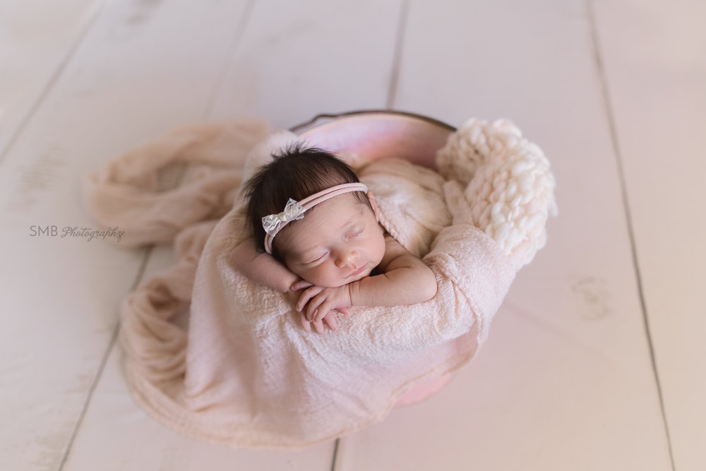 Newborn girl in pink bucket