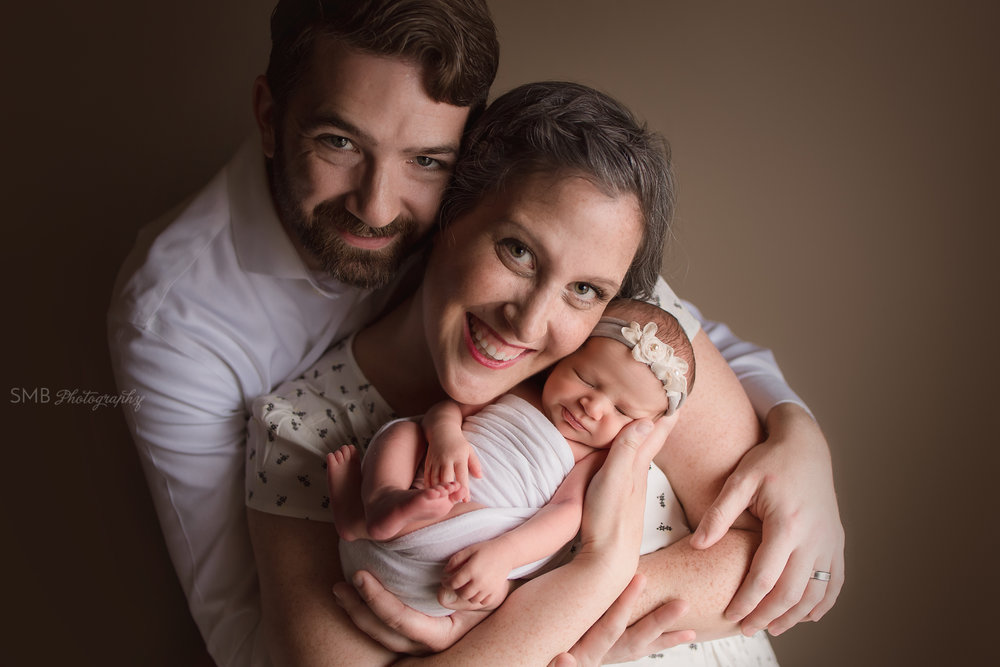 Mom& Dad holding newborn daughter smiling
