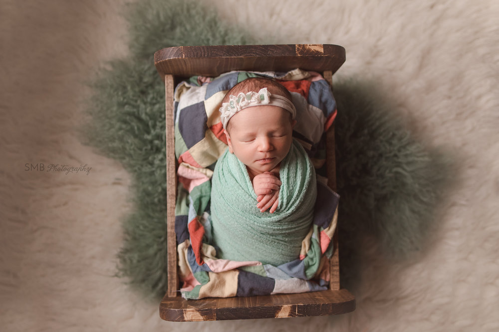 Newborn girl wearing green bonnet