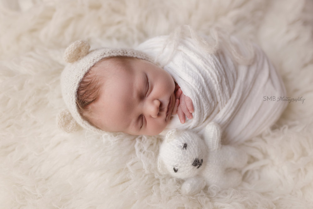 Newborn boy laying next to knitted bear