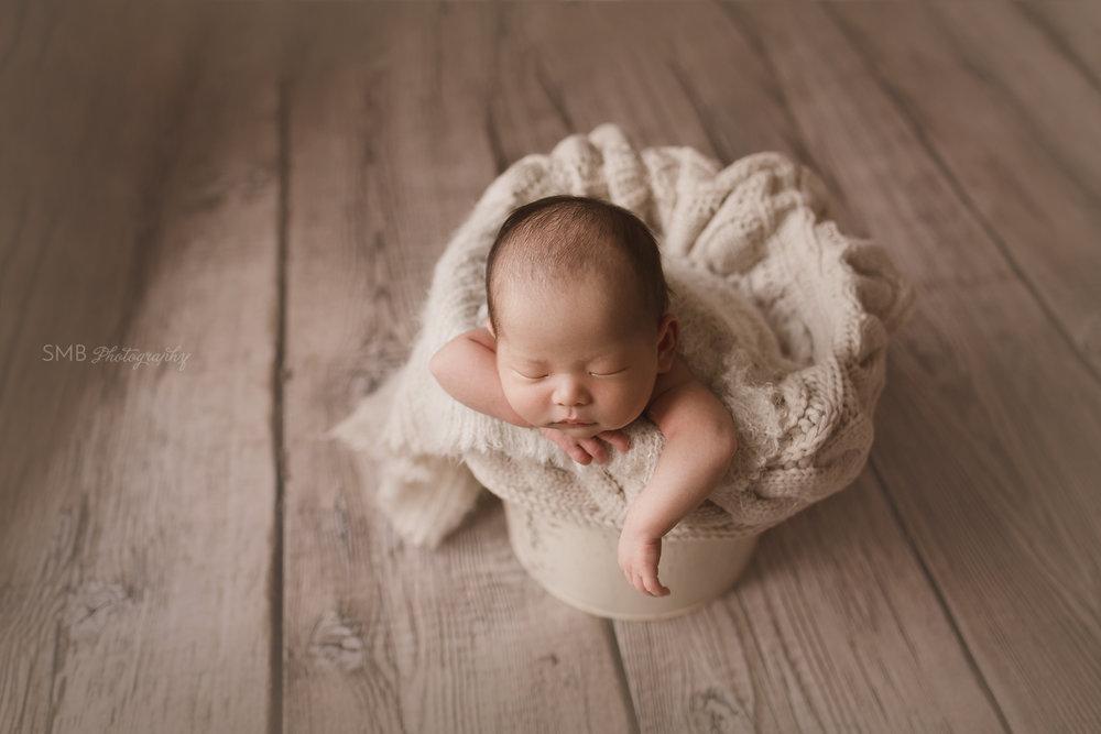 Newborn boy in cream colored bucket