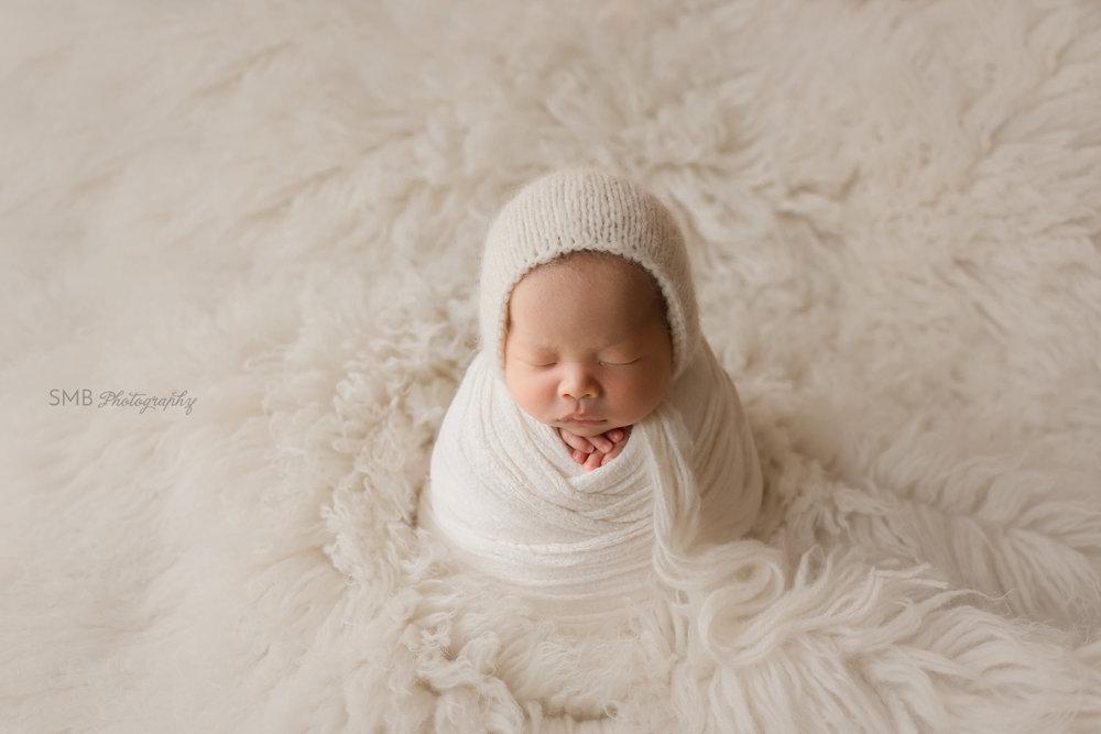 Baby boy wrapped on white flokati