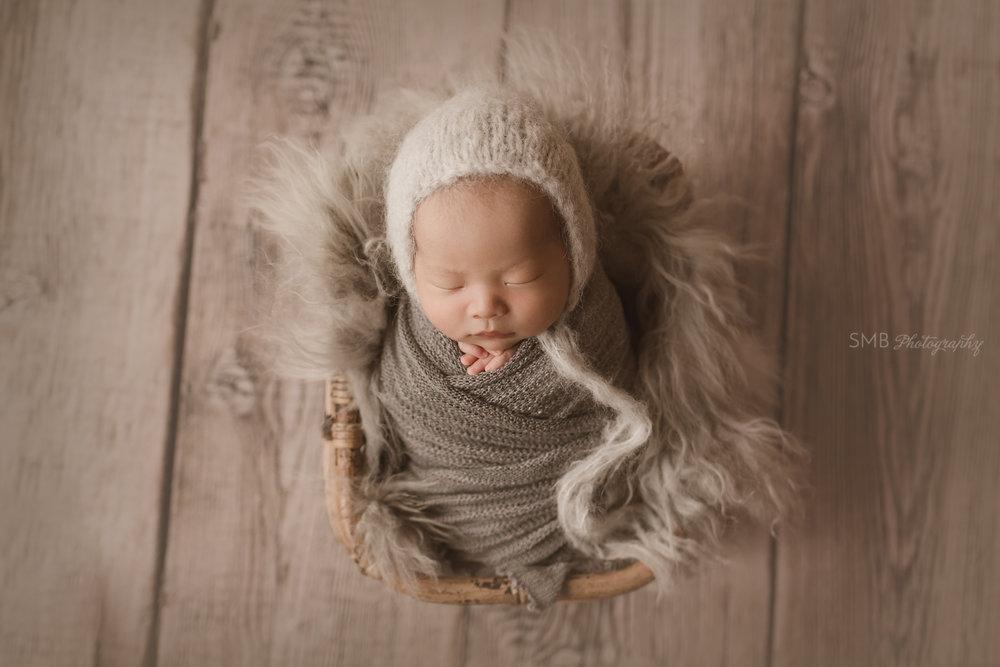 Newborn sleeping in basket on wood floor