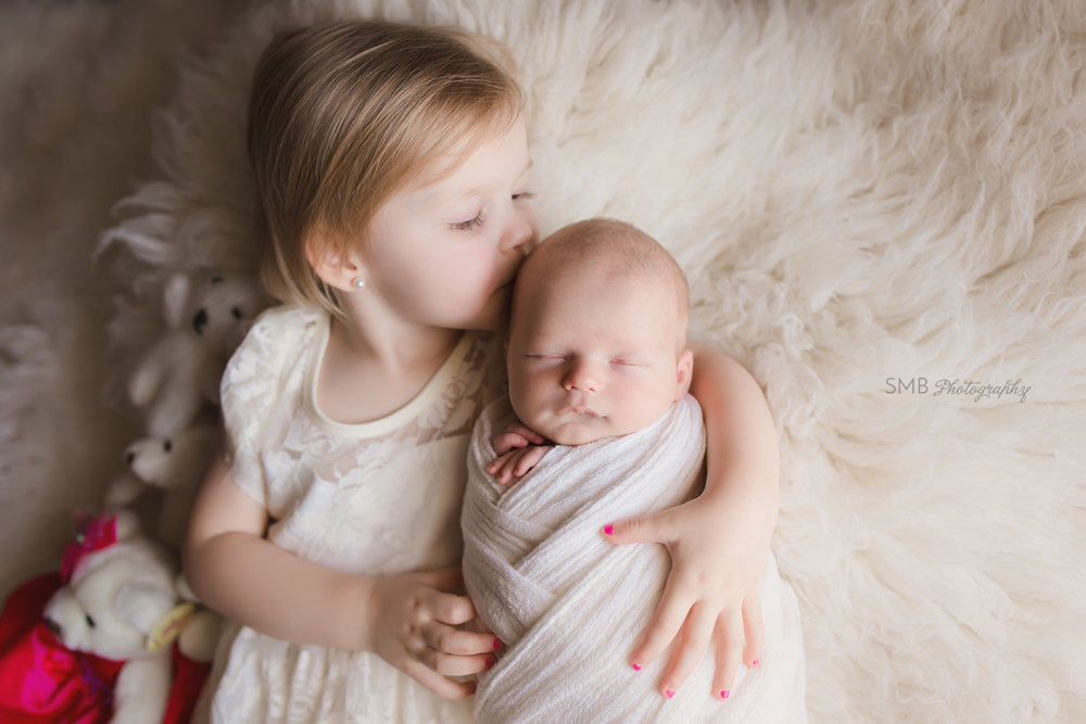 Big sister kissing newborn brother